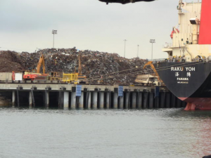 Piles of scrap metal waiting to load for export. The cranes load the hopper on the truck seen just to the left of the ship.