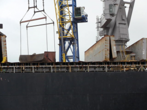 The crane takes the hopper off the truck and just dumps it into the ship's hold.